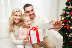 Family taking selfie with smartphone at christmas Stock Images