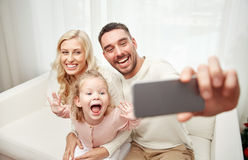 Family taking selfie with smartphone at home Royalty Free Stock Images