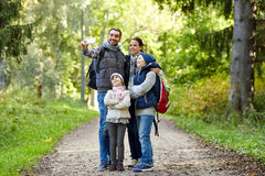 Family taking selfie with smartphone in woods. Travel, tourism, hike, technology and people concept - happy family with backpacks taking selfie by smartphone in Royalty Free Stock Photos