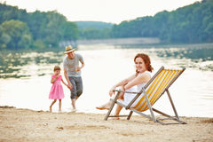 Family taking summer vacation at beach of a lake Stock Photos