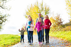 Family taking walk in autumn forest. Girls going ahead at family walk through the park in fall or autumn Stock Photography