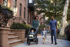 Family taking a walk down the street royalty free stock image