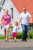 Family taking walk in front of home Stock Photo
