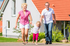 Family taking walk in front of home Stock Photography