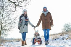 Family taking a winter walk in the snow. With child on sled Royalty Free Stock Photo