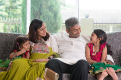 Family talk. Happy Indian family at home. Asian parents chit chatting with their kids, sitting on sofa. Parents and children indoor lifestyle stock photo