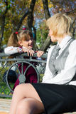 Mother and daughter talking. In autumn park Royalty Free Stock Image