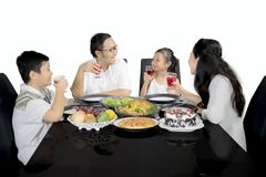 Family talking each other in the dining table Stock Photos