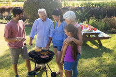 Family talking while preparing barbecue in the park. On a sunny day Stock Image