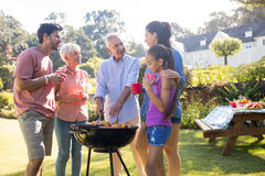 Family talking while preparing barbecue in the park. On a sunny day Stock Photography