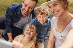 Family talking selfie on picnic. Beautiful women with family on picnic talking selfie at park. Couple with their two children making a self portrait at park stock images