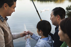 Family teaching a boy how to fish at a lake stock photos
