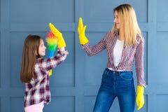 Family teamwork household chores mom kid high five. Family teamwork. home cleaning and household chores. mom and kid daughter giving high five stock photo