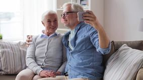 Happy senior couple with smartphone at home stock footage