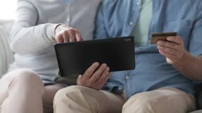 Senior couple with tablet pc and credit card stock footage