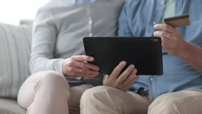 Senior couple with tablet pc and credit card stock video