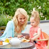 Mother and baby daughter with smartphone at cafe. Family and technology concept - happy mother and baby daughter using smartphone at cafe or restaurant terrace stock images