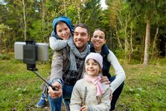 Family taking photo by selfie stick outdoors stock photography