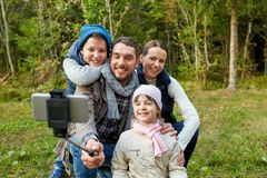 Family taking photo by selfie stick outdoors stock photos