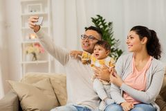 Mother and father with baby taking selfie at home. Family, technology, parenthood and people concept - happy mother and father with baby daughter taking selfie Stock Photography