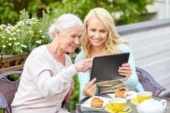 Daughter with tablet pc and senior mother at cafe Stock Photography