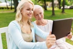 Daughter with tablet pc and senior mother at park Royalty Free Stock Photography