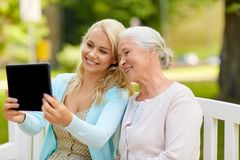 Daughter with tablet pc and senior mother at park. Family, technology and people concept - happy smiling young daughter with tablet pc computer and senior mother stock photo