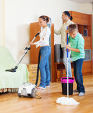 Family with teenage boy cleaning  in living room. Family of three with teenage boy cleaning with vacuum cleaner in living room Royalty Free Stock Image