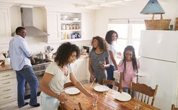 Family With Teenage Daughters Laying Table For Meal In Kitchen royalty free stock photo