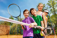 Family of tennis players standing next to the net Royalty Free Stock Photo