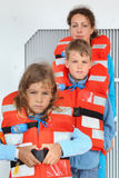 Family test their orange life jackets Royalty Free Stock Image