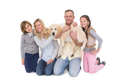 Family with their dog posing and smiling at camera together Stock Photo