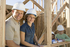 Family At Their Incomplete House. Portrait of happy family wearing hardhats at their incomplete house royalty free stock photo