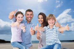 Family with their thumbs up on the beach Royalty Free Stock Photo