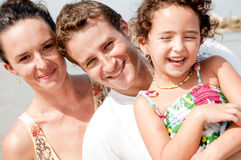 Family of three. Parents and daughter smiling in the beach stock image