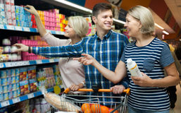 Family of three adults are choosing yogurt in the dairy departme. Happy family of three adults are choosing yogurt in the dairy department store Royalty Free Stock Photos