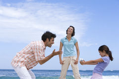 Family of three on beach, daughter (6-8) with camcorder, low angle view Royalty Free Stock Images