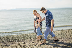 Family of three on beach having fun together Royalty Free Stock Image