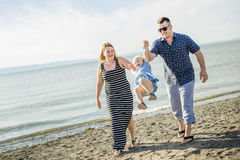 Family of three on beach having fun together Royalty Free Stock Photos