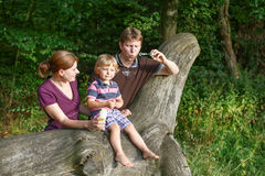 Family of three blowing soap bubbles together in summer forest Royalty Free Stock Images