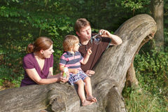 Family of three blowing soap bubbles together in summer forest Stock Images