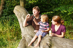 Family of three blowing soap bubbles together in summer forest Stock Photos