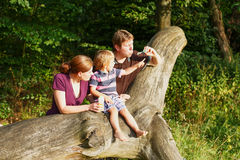Family of three blowing soap bubbles together in summer forest Royalty Free Stock Photo