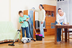 Family of three with  boy cleaning  in  room Royalty Free Stock Photos