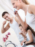 Family of three brush their teeth Stock Photos