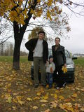 Family of three and car and autumn. Leaves royalty free stock image