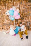 Family of three celebrates daughter`s birthday one year inside the room sitting on the floor against the background of the wooden Stock Image