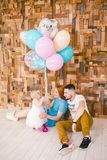 Family of three celebrates daughter`s birthday one year inside the room sitting on the floor against the background of the wooden royalty free stock photo
