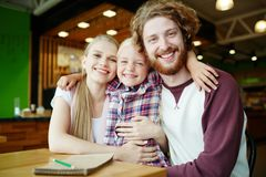 Family of three. Cheerful child embracing her parents while spending time in cafe stock photo