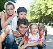 Family and three children in park. Royalty Free Stock Photos